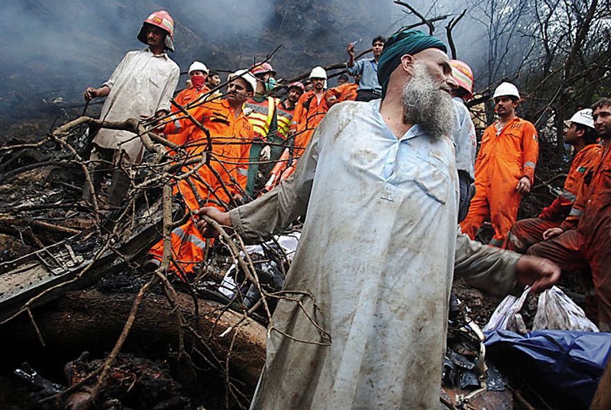 Pakistani rescue workers look for survivors amid the wreckage of a plane that crashed in Islamabad, Pakistan on Wednesday, July 28, 2010. A government official says all 152 people on board the plane that crashed in the hills surrounding Pakistan's capital were killed. (AP Photo/Irfan Haider)