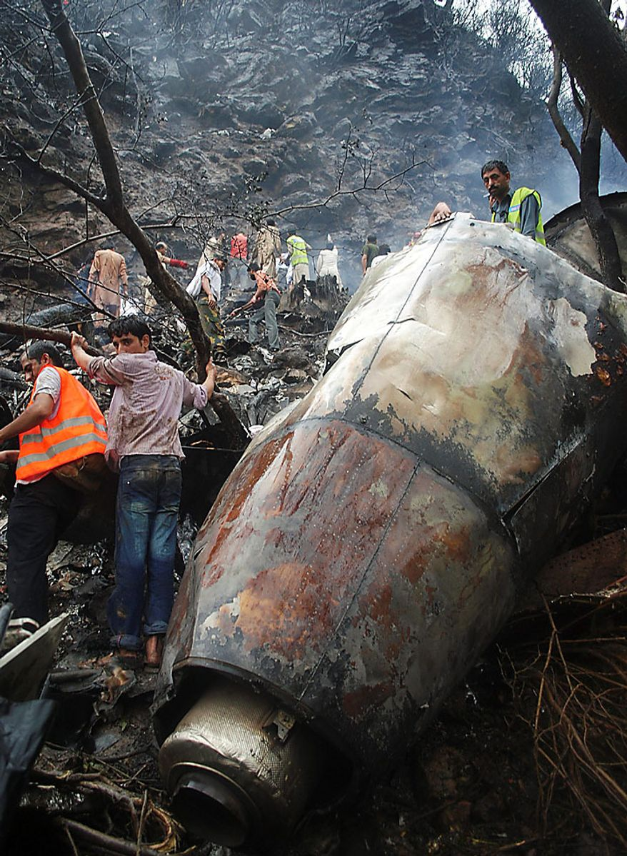 Pakistani rescuers surround the wreckage of a plane that crashed in Islamabad, Pakistan on Wednesday, July 28, 2010. A government official says all 152 people on board the plane that crashed in the hills surrounding Pakistan's capital were killed. (AP Photo/Irfan Haider)
