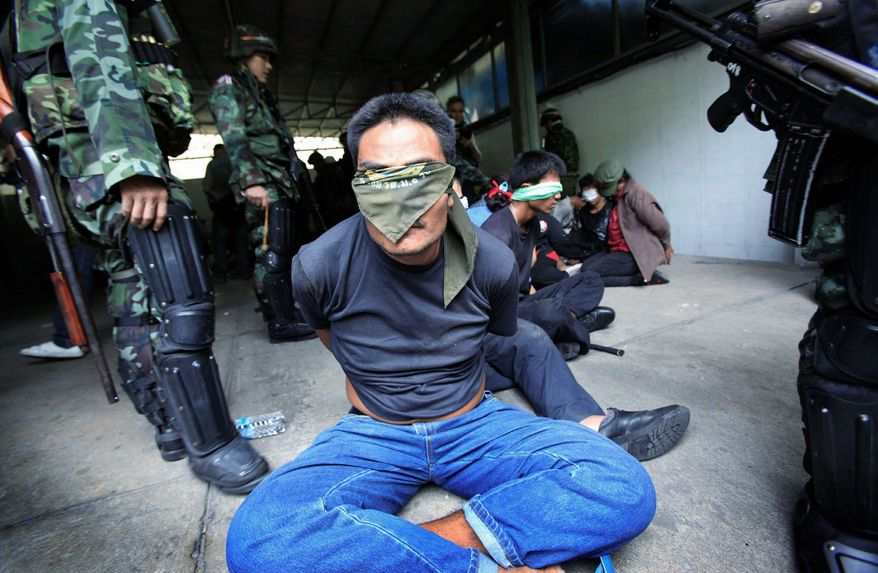 ASSOCIATED PRESS PHOTOGRAPHS Thai soldiers hold anti-government protesters in their encampment in Bangkok on May 19, ending a nine-month showdown that caused up to 90 deaths.