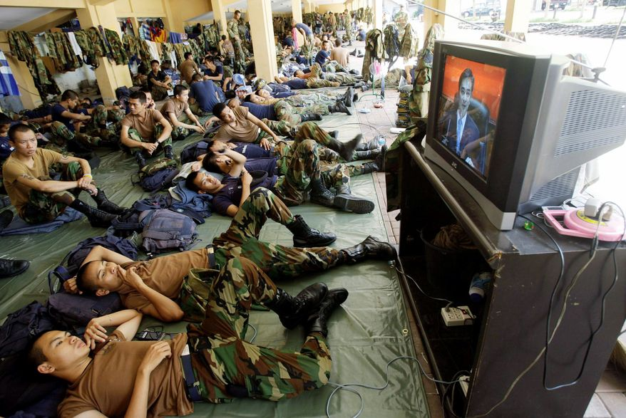 Soldiers watch Mr. Abhisit's April 12, 2009, speech from Government House in Bangkok announcing a state of emergency aimed at stemming anti-government protests across the country.