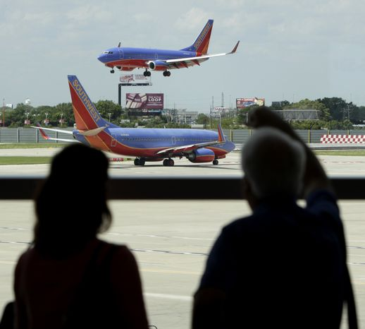 In this photo taken Friday, June 25, 2010, passengers traveling on Southwest Airlines watch as one plane waits to takeoff and another lands at Midway Airport in Chicago. Southwest Airlines Co. added an upbeat note to a strong quarter for the airline industry on Thursday, July 29, 2010, by reporting a $112 million profit for spring and early summer. (AP Photo/Charles Rex Arbogast)