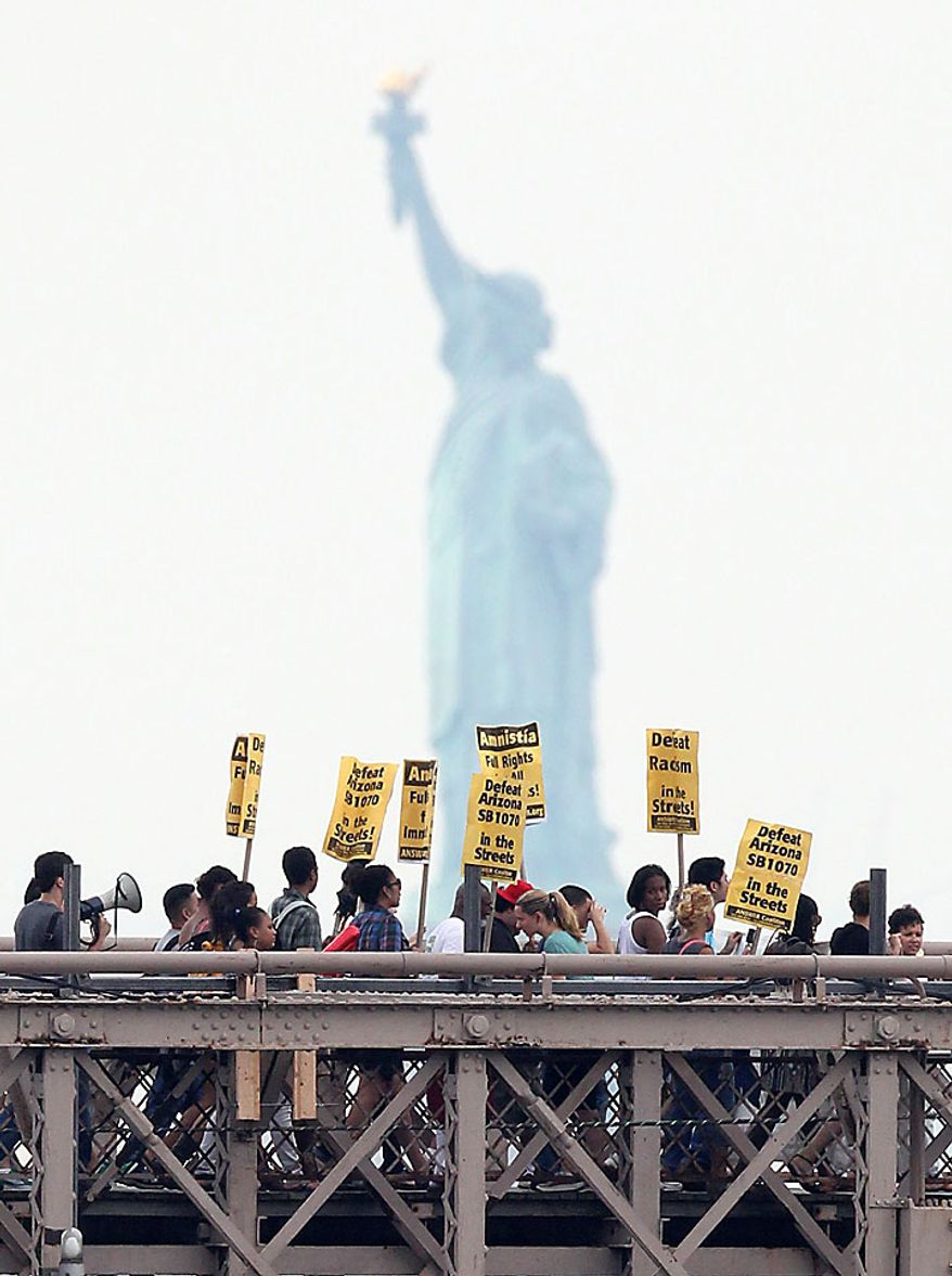 With the Statue of Liberty behind them, a coalition of immigrant groups and their supporters march in the hundreds across the Brooklyn Bridge, Thursday July 29, 2010, in New York. Protesters are calling for the full repeal of Arizona's immigration law, saying it fuels a climate of racism. (AP Photo/Seth Wenig)