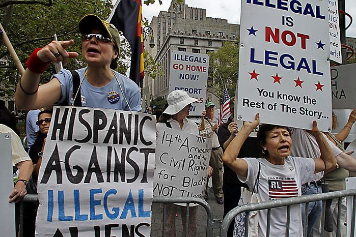 ** FILE ** A group supporting Arizona's immigration law, which opponents say fuels a climate of racism, shout at a coalition of immigrant groups and their supporters calling for a full repeal of the law on Thursday, July 29, 2010, in New York. (AP Photo/Bebeto Matthews)