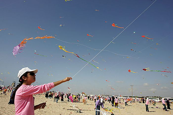 Thousands of Palestinian children fly kites along the beach during a U.N.-sponsored summer camp in the northern Gaza Strip on Thursday, July 29, 2010. The children claimed a world record, flying thousands of kites at the same time. About 8,000 children attended in the event, Khalil el-Halabi, education program head at the U.N. Relief an