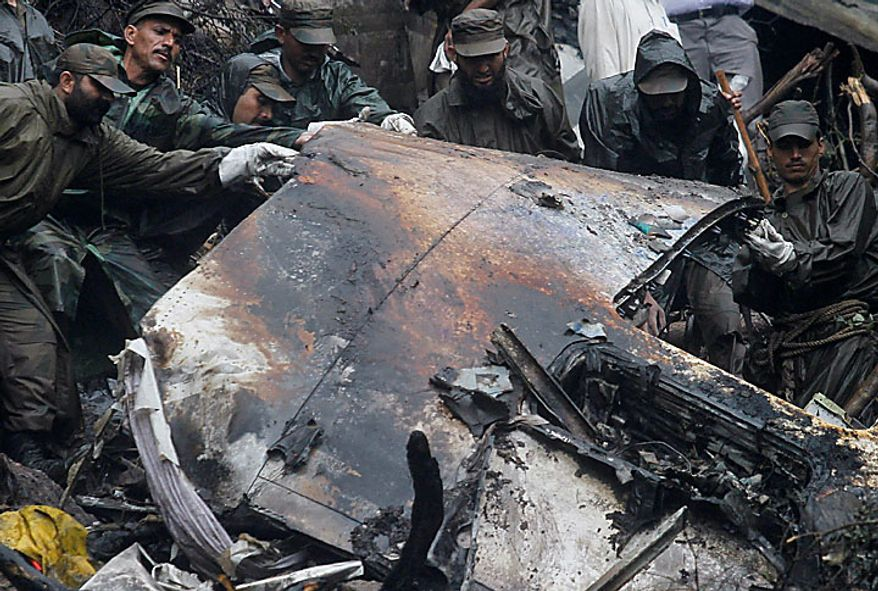 Pakistani army troops on Thursday, July 29, 2010, remove a piece of wreckage at the site of Wednesday's deadly plane crash in the mountains surrounding Islamabad, Pakistan. The Airbus A321 operated by Pakistani carrier Airblue crashed into hills overlooking the country's capital, Islamabad, during stormy monsoon weather, killing all 152 people on board. (AP Photo/Anjum Naveed)