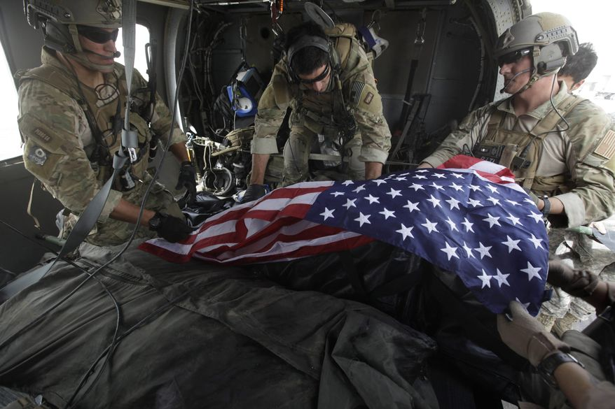 In this photograph made on Thursday July 29, 2010, upon landing after a helicopter rescue mission, Tech. Sgt. Jeff Hedglin, right, an Air Force Pararescueman, or PJ, drapes an American flag over the remains of the first of two U.S. soldiers killed minutes earlier in an IED attack, assisted by fellow PJs, Senior Airman Robert Dieguez, center, and 1st Lt. Matthew Carlisle, in Kandahar province, southern Afghanistan. July 2010 was the deadliest month for American forces in the nearly 9-year Afghan War. (AP Photo/Brennan Linsley)
