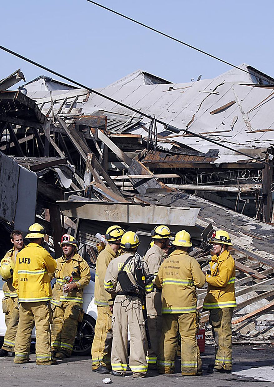 Members of the Los Angeles Fire Department stand at the site where a suspected natural gas explosion occurred Friday July 30, 2010 in Los Angeles. The explosion collapsed part of the building and hurled two workers into the street, killing one and leaving the other in critical condition, fire officials said. (AP Photo/Nick Ut)