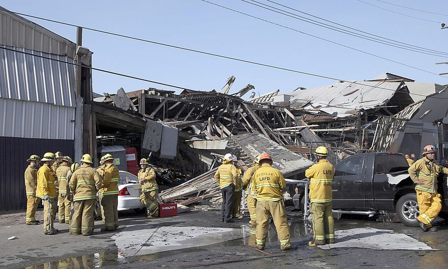 Los Angeles Fire Department firefighters are shown at a building site where a suspected natural gas explosion occurred Friday, July 30, 2010 in Los Angeles. The explosion collapsed part of the building and hurled two workers into the street, killing one and leaving the other in critical condition, fire officials said. (AP Photo/Nick Ut)