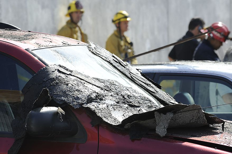 Roofing material covers nearby cars after a suspected natural gas explosion occurred at a welding shop, collapsing part of the building and hurling two workers into the street, killing one and leaving the other in critical condition, Friday, July 30, 2010, in Los Angeles. (AP Photo/Gus Ruelas)