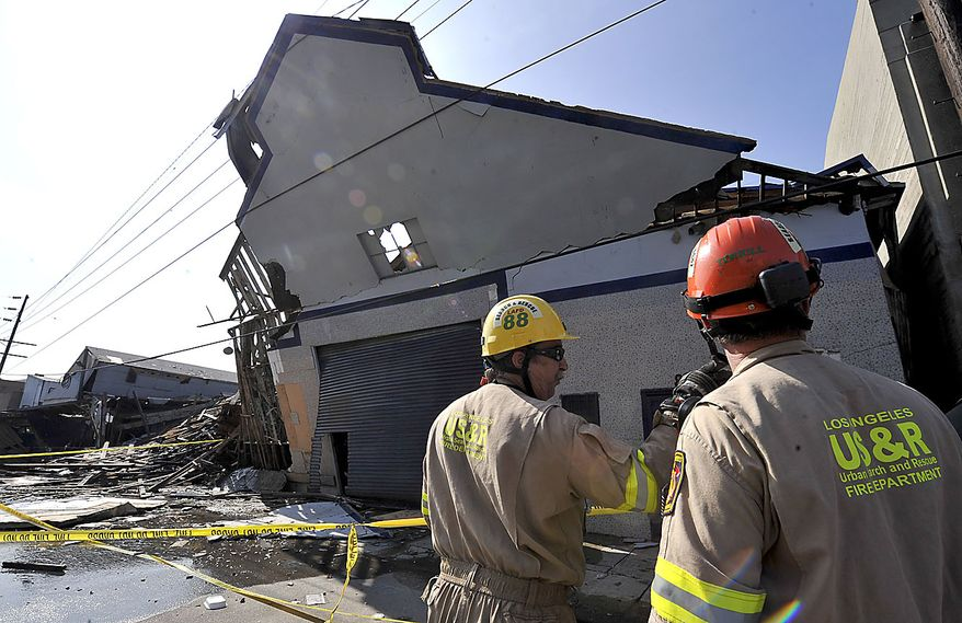 Members of the Los Angeles Fire Department urban search and rescue team survey damage after a suspected natural gas explosion at a welding shop collapsed part of the building hurling two workers into the street, killing one and leaving the other in critical condition, Friday, July 30, 2010, in Los Angeles. (AP Photo/Gus Ruelas)