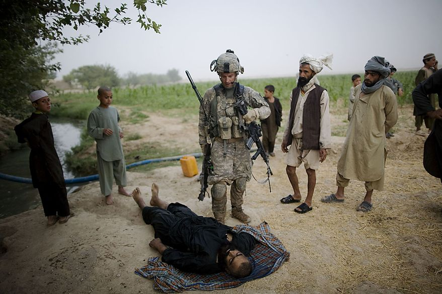 In this July 28, 2010, file photo, U.S. Army Lt. Christopher Babcock looks at the body of a suspected Taliban fighter killed by U.S. soldiers from 1-320th Alpha Battery, 2nd Brigade of the 101st Airborne Division, while local people protest the man was a farmer from Samir Kalacha village in the volatile Arghandab Valley, Kandahar, Afghanistan. (AP Photo/Rodrigo Abd, File)