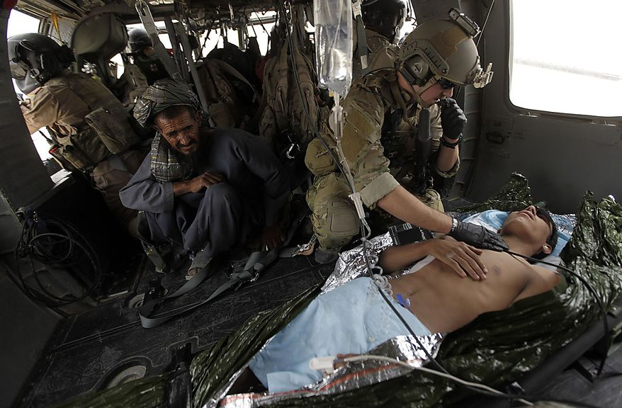 "During a helicopter rescue mission en route to a military hospital, Staff Sgt. Brandon Smith, a Pararescueman, or ""PJ,"" of the 58th Rescue Squadron, treats an Afghan National Army soldier with a gunshot wound to the back, in Kandahar province, southern Afghanistan, Thursday, July 29, 2010. The PJs and helicopter aircrews are part of the U.S. Air Force's 451st Air Expeditionary Wing based at Kandahar Air Field, which provides a variety of air assets in southern Afghanistan. (AP Photo/Brennan Linsley)"