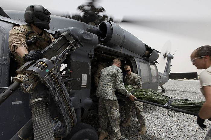 A 50 calibre U.S. Air Force door gunner waits as a patient is loaded onto his helicopter during a rescue mission for a wounded Afghan soldier in the Arghandab Valley, Kandahar province, southern Afghanistan, Thursday, July 29, 2010. Rescue teams one part of the U.S. Air Force's 451st Air Expeditionary Wing in southern Afghanistan. (AP Photo/Brennan Linsley)