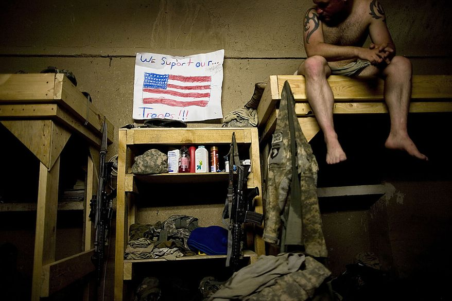 In this July 29, 2010, file photo, Spc. Dallas Purdy from Hockley, Texas, hangs a message of support from friends Ashley and Katie Daniels while serving with the 1-320th Alpha Battery, 2nd Brigade of the 101st Airborne Division at COP Nolen, in the volatile Arghandab Valley, Kandahar, Afghanistan. (AP Photo/Rodrigo Abd, File)
