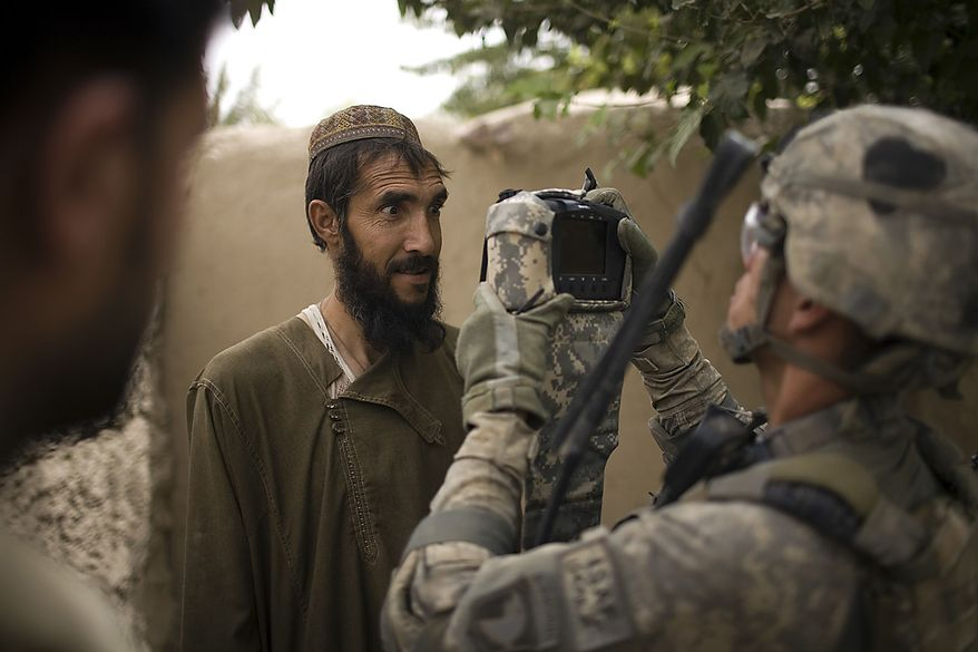 U.S. Army Spc. Brad Parrish, of Spokane, Wash., from the 1-320th Alpha Battery, 2nd Brigade of the 101st Airborne Division, takes an eye scan of an Afghan villager in Samir Kalacha, in the volatile Arghandab Valley, Kandahar, Afghanistan, Wednesday, July 28, 2010. (AP Photo/Rodrigo Abd)