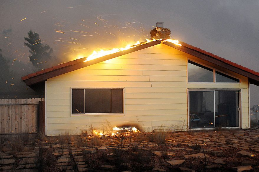 A house catches on fire from a fast moving wildfire on Thursday, July 29, 2010, in Leona Valley, Calif.  About 2,000 homes in the community of Leona Valley and parts of Palmdale areas were under evacuation Friday, according to Los Angeles County Fire. (AP Photo AP/Dave Mills)