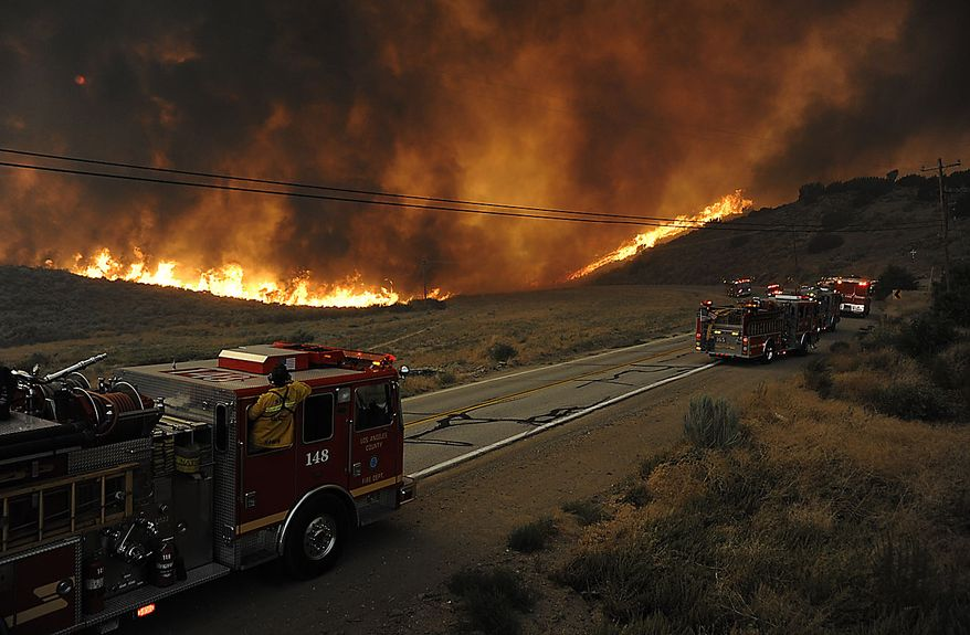 Fire engines pause as flames from a fast moving wildfire approach Elizabeth Lake Road in the Leona Valley near Palmdale, Calif., on Thursday, July 29, 2010. Mandatory evacuations were issued for the community of Leona Valley on Thursday evening, Los Angeles County Fire Inspector Matt Levesque said. (AP Photo/Dan Steinberg)