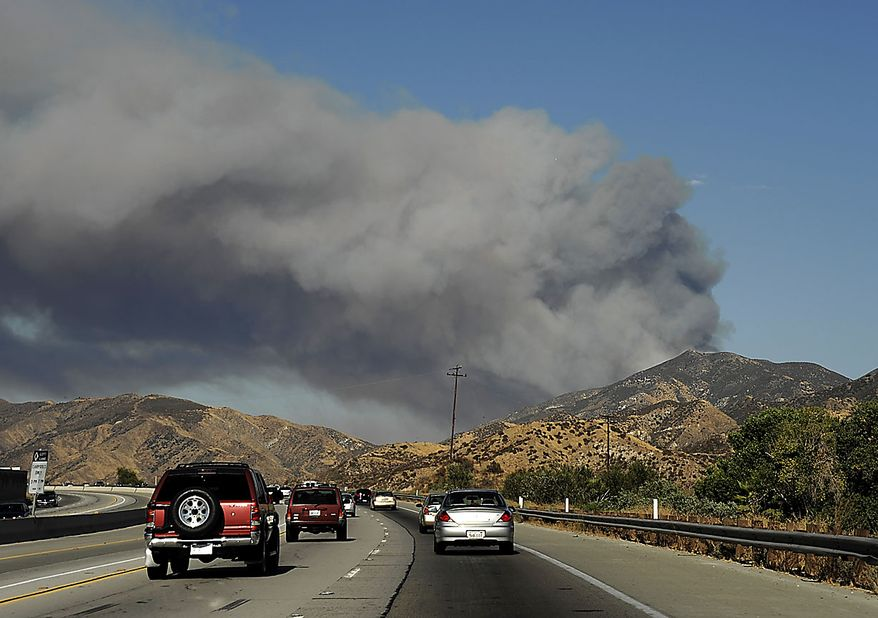 Seen from Freeway 14, a fast moving wildfire burns near Acton, Calif. on Thursday, July 29, 2010. (AP Photo/Dan Steinberg)
