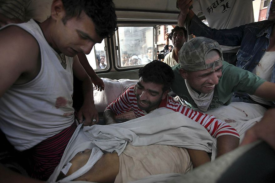 Relatives and friends of Showket Ahmad wail near his body inside an ambulance outside a local hospital in Srinagar, India, Friday, July 30, 2010. Paramilitary soldiers fired on hundreds of demonstrators in Indian Kashmir on Friday, killing two men and wounding at least 12 others, police said as protests against Indian rule spread across the region. Showket was one of two civilian killed during a protest in Sopore, some 31 miles northwest of Srinagar. (AP Photo/Dar Yasin)