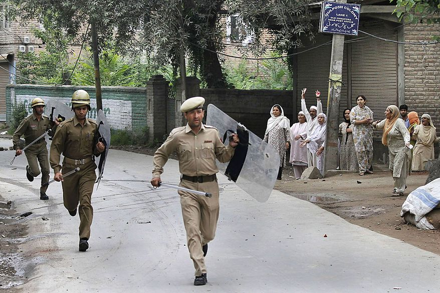 Indian police run for cover as Kashmiri Muslims shout pro-freedom slogans during a protest in Srinagar, India, Friday, July 30, 2010. Massive clashes erupted in Indian Kashmir's main city Friday after two men were wounded as paramilitary soldiers fired on a group of anti-India protesters, police and locals said. (AP Photo/Dar Yasin)