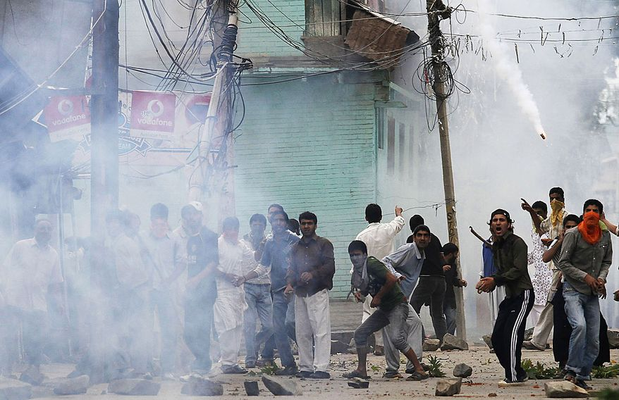 Kashmiri Muslim protesters throw rocks and bricks at Indian police under tear gas smoke during a protest in Srinagar, India, Friday, July 30, 2010. Massive clashes erupted in Indian Kashmir's main city Friday after two men were wounded as paramilitary soldiers fired on a group of anti-India protesters, police and locals said. (AP Photo/Dar Yasin)
