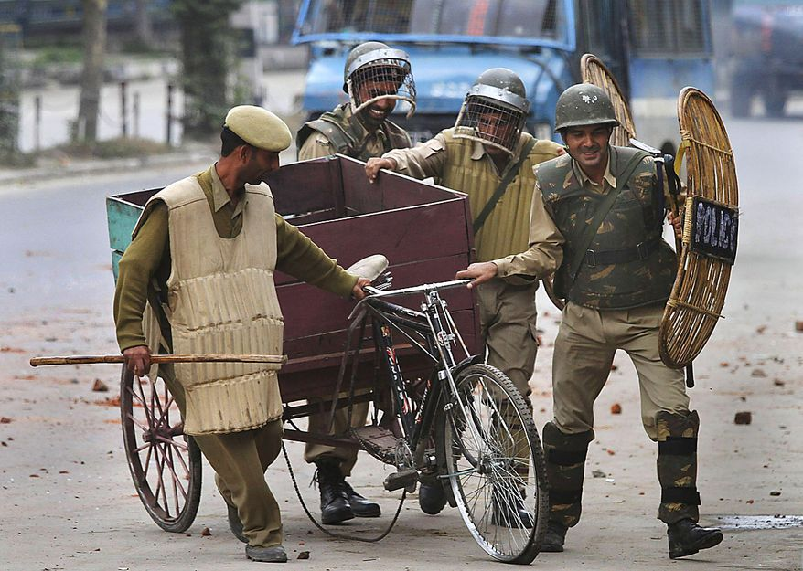 Indian police and paramilitary soldiers remove a cycle rickshaw used as road blockade by protesters during a protest in Srinagar, India, Friday, July 30, 2010. Massive clashes erupted in Indian Kashmir's main city Friday after two men were wounded as paramilitary soldiers fired on a group of anti-India protesters, police and locals said. (AP Photo/Dar Yasin)