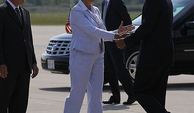 Michigan Gov. Jennifer Granholm, center, and her husband Daniel Mulhearn, left, greet President Barack Obama upon his arrival at Detroit Wayne County Airport in Detroit, Friday, July 30, 2010. (AP Photo/Pablo Martinez Monsivais)