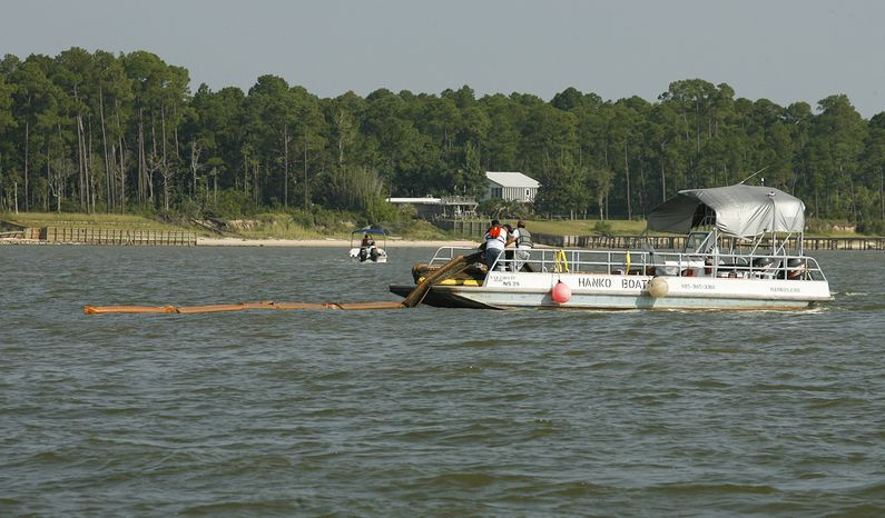 Workers remove boom from Mobile Bay south of Fowl River, Ala., Friday, July 30, 2010. Boom is being removed in preparation for the height of hurricane season. (AP Photo/Press-Register, Mike Kittrell)