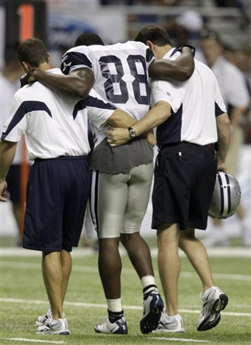 Dallas Cowboys wide receiver Dez Bryant is assisted off the field by trainers after injuring his right ankel area during an afternoon practice at Cowboys training camp Friday, July 30, 2010, in San Antonio. The injury was suffered when Bryant, who was trying to reach a pass intended for him, got tangled with cornerback Orlando Scandrick. (AP Photo/Tony Gutierrez)