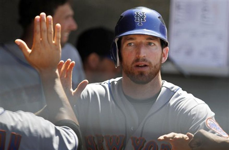 New York Mets' Ike Davis, right, gets high-fives from his teammates in the dugout after scoring on an RBI single by Rod Barajas during the sixth inning of a baseball game against the Los Angeles Dodgers, Saturday, July 24, 2010 in Los Angeles. (AP Photo/John Lazar)
