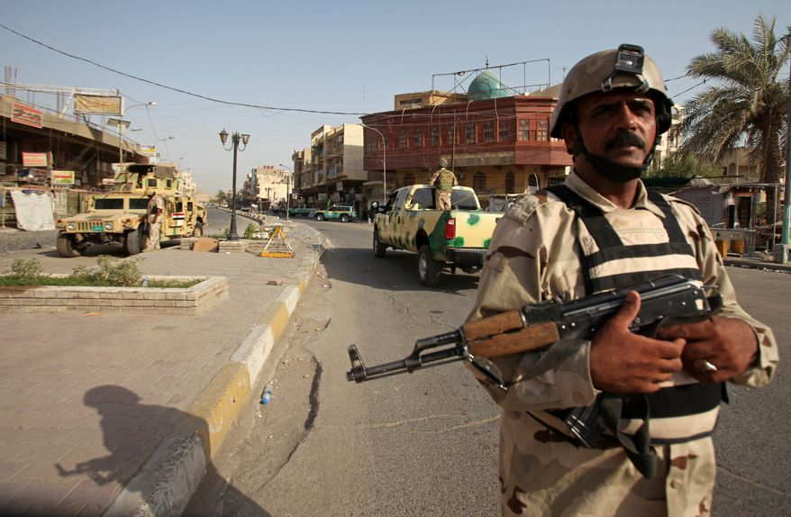 Iraqi soldiers secure a street in the Azamiyah neighborhood in Baghdad on Saturday, July 31, 2010, after authorities announced a partial lifting of a curfew imposed on the Sunni neighborhood on Thursday following a brazen daylight attack by al Qaeda militants. (AP Photo/Khalid Mohammed)