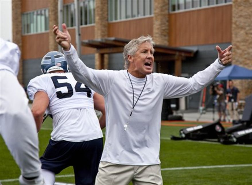Seattle Seahawks head coach Pete Carroll urges on the crowd as well as players during the opening day of the NFL football training camp on Saturday, July 31, 2010, in Renton, Wash. (AP Photo/John Froschauer)