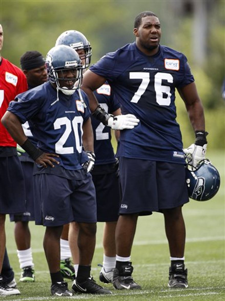 FILE - In this Auprl 30, 2010, file photo,  Seattle Seahawks first-round draft pick tackle Russell Okung, right, stands next to running back Justin Forsett, left, during rookie football minicamp at the team's headquarters in Renton, Wash. The agent for sixth-overall draft choice Okung says he is working to ensure Seattle's replacement for left tackle Walter Jones is on the field when Seahawks training camp begins on Saturday.  (AP Photo/Ted S. Warren, File)
