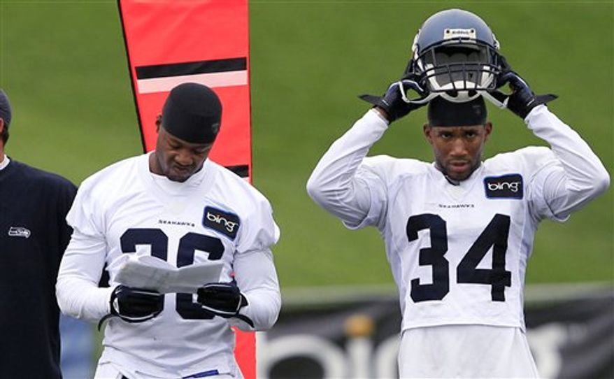 Seattle Seahawks' Lawyer Milloy, left, looks over a play sheet as he stands on the sidelines with Roy Lewis during NFL football practice Monday, Aug. 2, 2010, in Renton, Wash. In 1999, Pete Carroll was struck with how hard and how smart Milloy played safety for him when he coached New England. Now back in the NFL leading the Seahawks, Carroll has called the 36-year-old back for yet another season. (AP Photo/Elaine Thompson)