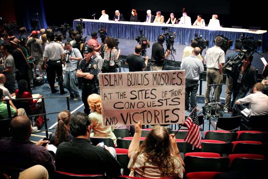 Linda Rivera holds up a sign in opposition to the proposed mosque at 45-47 Park Place during a meeting of the Landmarks Preservation Commission, where the panel voted on the landmark status of the 152-year-old building on Tuesday in New York. The commission voted unanimously not to landmark the building, making way for the construction of the mosque. (Associated Press)