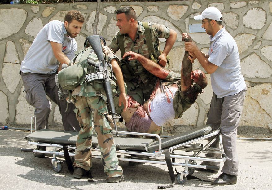 Civil defense workers and Lebanese soldiers (below) carry an injured soldier in the village of Adaisseh on Tuesday. (Associated Press)