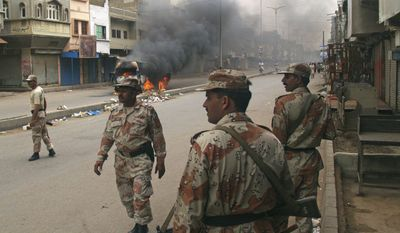 Pakistani para military troops gather near a vehicle set on fire by angry mob following the killing of a local leader of the Muttahida Quami Movement in Pakistan on Tuesday, Aug. 3, 2010. Gunmen killed dozens of people in Pakistan's largest city after the assassination of a lawmaker, officials said Tuesday. (AP Photo/Shakil Adil)