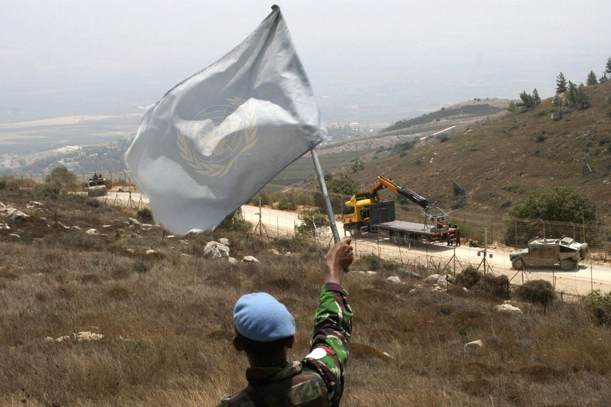 A U.N. peacekeeper waves a U.N. flag as Israeli troops patrol the border in the southern border village of Adaisseh, Lebanon, Tuesday, Aug. 3, 2010. A senior Israeli officer, two Lebanese soldiers and a journalist. were killed in the clashes. Tuesday's fighting was the most serious since a fierce war four years ago. (AP Photo/Ronith Daher)