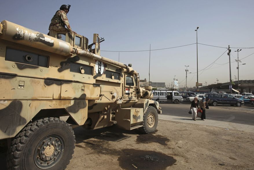 An Iraqi army soldier on top of an armored vehicle stands guard at the scene of an attack on a checkpoint in Baghdad on Tuesday, Aug 3, 2010. Suspected al-Qaida militants killed 5 Iraqi soldiers in the brazen dawn attack and planted the terror group's black banner before fleeing the scene, officials said. (AP Photo/Karim Kadim)