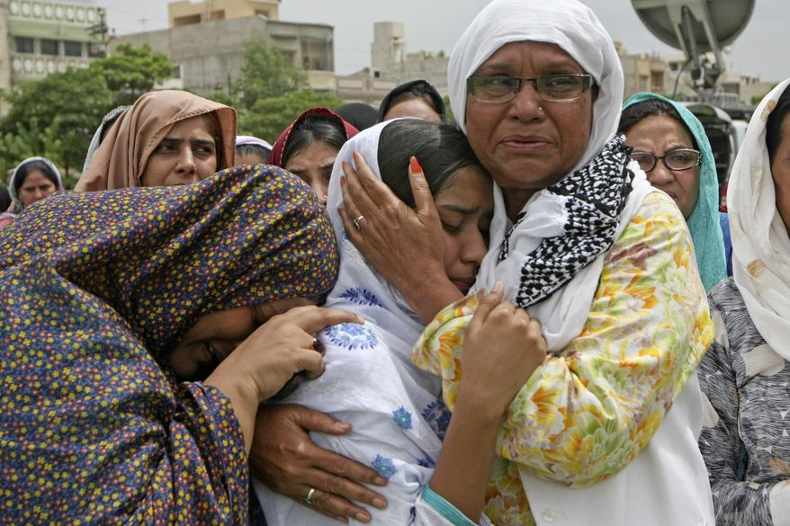 Family members of slain local leader of the Muttahida Quami Movement Raza Haider who was killed by unknown gunmen, cry during his funeral in Karachi, Pakistan on Tuesday, Aug. 3, 2010. Gunmen killed dozens of people in Pakistan's largest city after the assassination of a lawmaker, officials said Tuesday. (AP Photo/Fareed Khan)