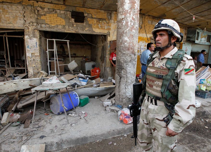 An Iraqi solider stands guard at the scene of an attack in Kut, southeast of Baghdad, on Wednesday. A car bomb ripped through a market in the deadliest of a series of attacks that killed and injured scores on Tuesday, officials said. (Associated Press)