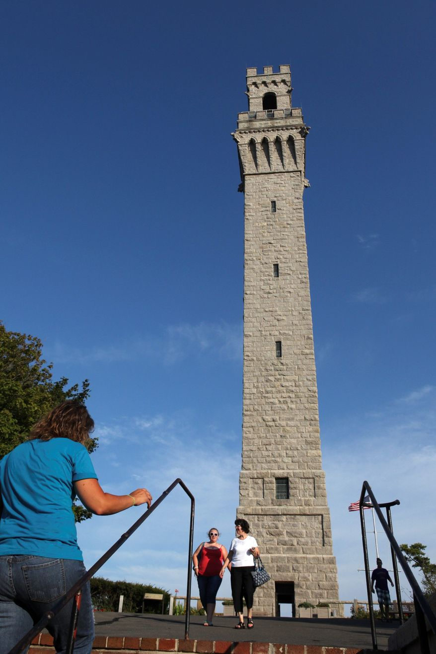 Visitors walk near the Pilgrim Monument in Provincetown, Mass., on the tip of Cape Cod. The tower will mark the 100th anniversary of its dedication on Thursday. (Associated Press)