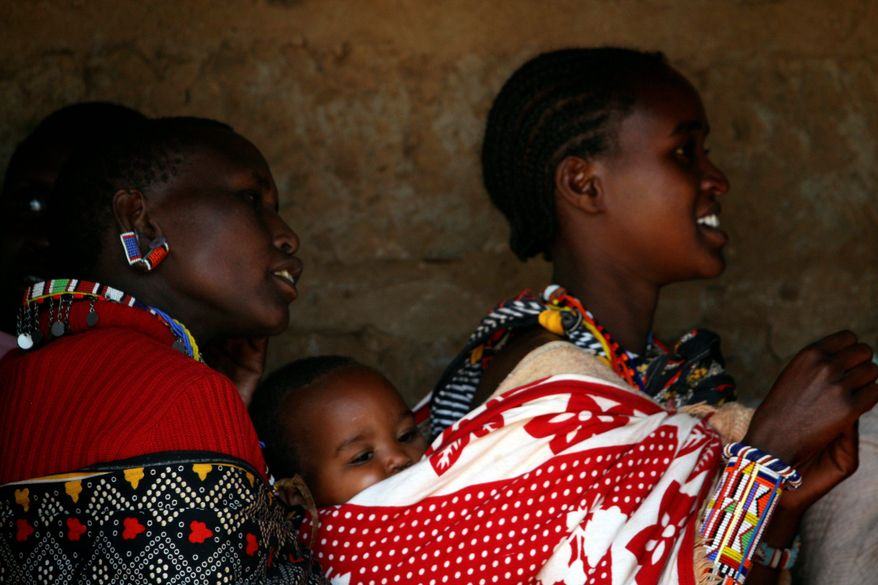 Kenyan Masai women wait in line to cast their vote at a polling station in Ngong, Kenya. Police were deployed across the country and though the polls were crowded, officials reported no violence. (Associated Press)