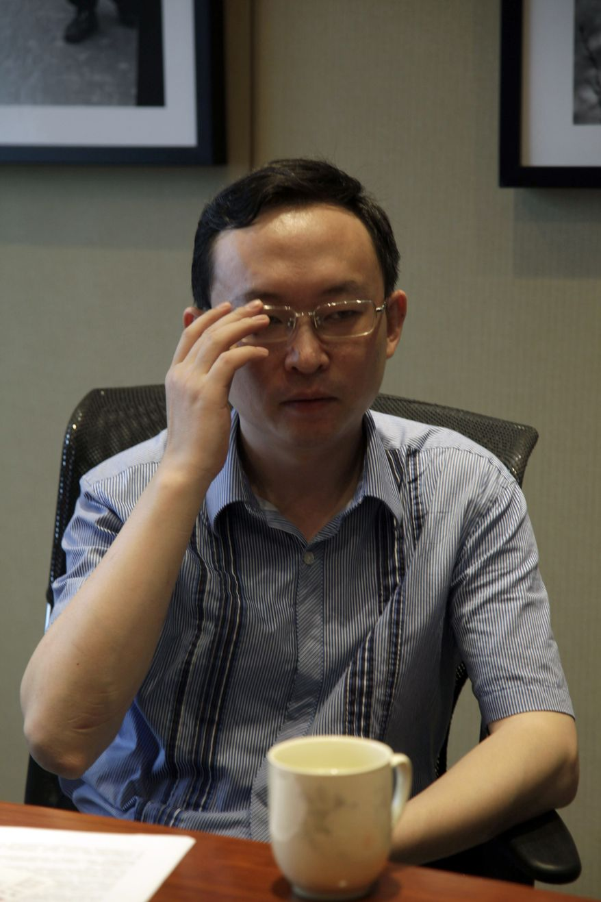 Chinese writer Yu Jie adjusts his glasses during an interview in Beijing, China, Wednesday, Aug. 4, 2010. Mr. Yu, the author of a book unusually critical of China's premier said Wednesday it will be published this month in Hong Kong despite police threats that he could be put in prison. (AP Photo/Ng Han Guan)