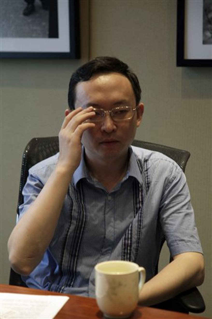 "Chinese writer Yu Jie, speaks near a print out of the cover of his book ""China's Best Actor: Wen Jiabao,"" during an interview in Beijing,  China, Wednesday, Aug. 4, 2010. The author of the book unusually critical of China's premier said Wednesday it will be published this month in Hong Kong despite police threats that he could be put in prison. (AP Photo/Ng Han Guan)"