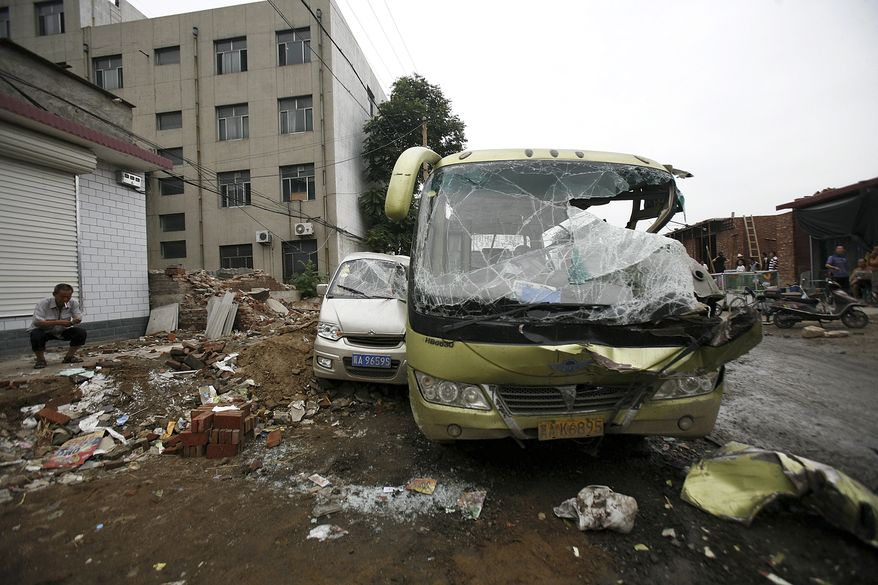 ** FILE ** A man smokes near smashed vehicles at Yuanshi county, in north China's Hebei province, after a drunken shovel loader driver went on a rampage, smashing into shops and vehicles and killing 17 people on Sunday, Aug. 2, 2010. (AP Photo)