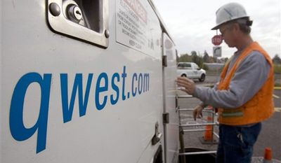 FILE - In this Oct. 28, 2009 file photo, Qwest employee Scott Naylin prepares to work on underground cables in Portland, Ore. Qwest Communications International Inc., which has agreed to be acquired by a smaller phone company, on Wednesday, Aug. 4, 2010, said its second-quarter earnings fell 26 percent as customers continued to cancel landlines, and it signed up few new broadband customers. (AP Photo/Don Ryan, file)