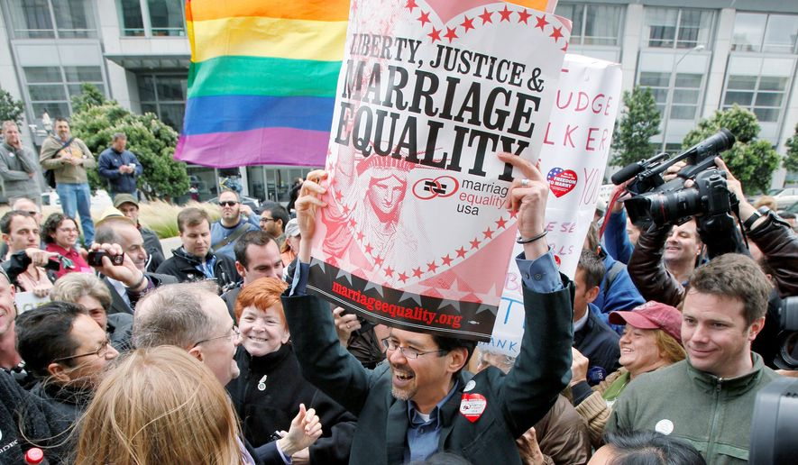 VICTORY PARTY: In San Francisco on Wednesday, Stuart Gaffney holds up a sign while celebrating a court's decision to overturn Proposition 8. (Associated Press)