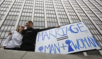 Nadia Chayka and her fiance, Luke Otterstad, both proponents of Proposition 8, hold up a sign outside of the Phillip Burton Federal Building in San Francisco on Wednesday. Chief U.S. District Judge Vaughn Walker ruled that Proposition 8, by defining marriage as the union of one man and one woman, violated the Due Process and Equal Protection clauses of the Constitution. (Associated Press)