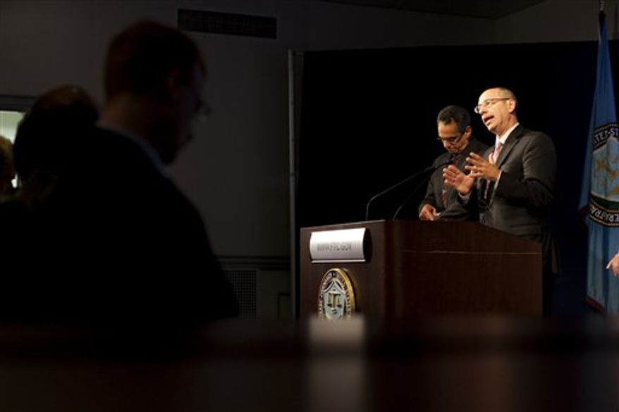 FTC Chairman Jon Leibowitz is seen through the curtains during a news conference at the Federal Trade Commission (FTC) in Washington on Aug. 4, 2010, to discuss the Intel antitrust case. (Associated Press)